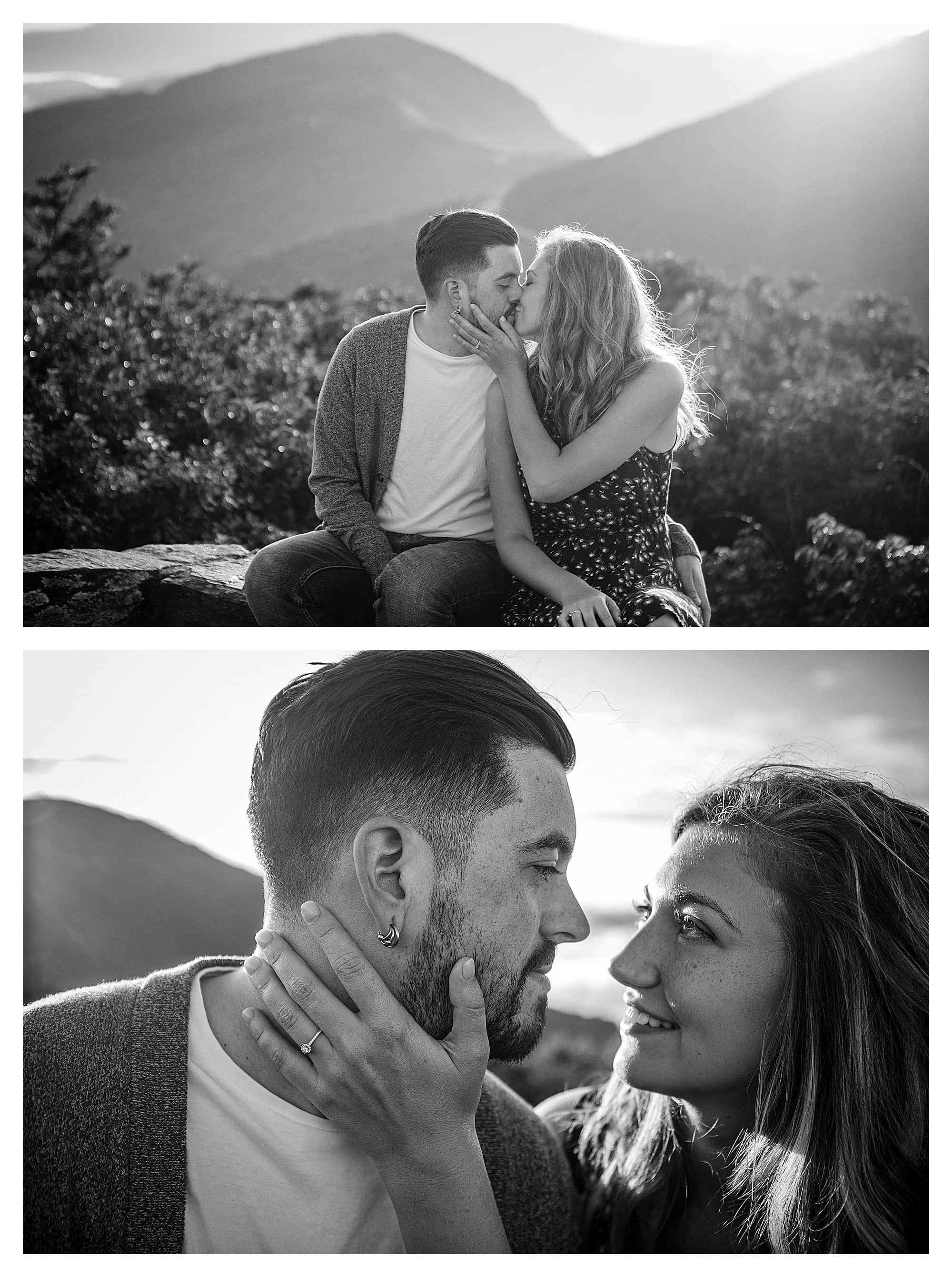 Black and white phots of engaged couple kissing while sitting on brick wall with mountains in background