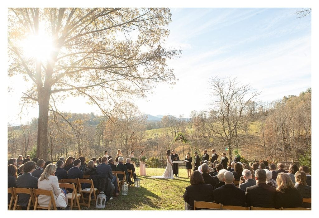 Wedding ceremony outdoors with mountains and green fields in background on sunny day - kathy beaver photography