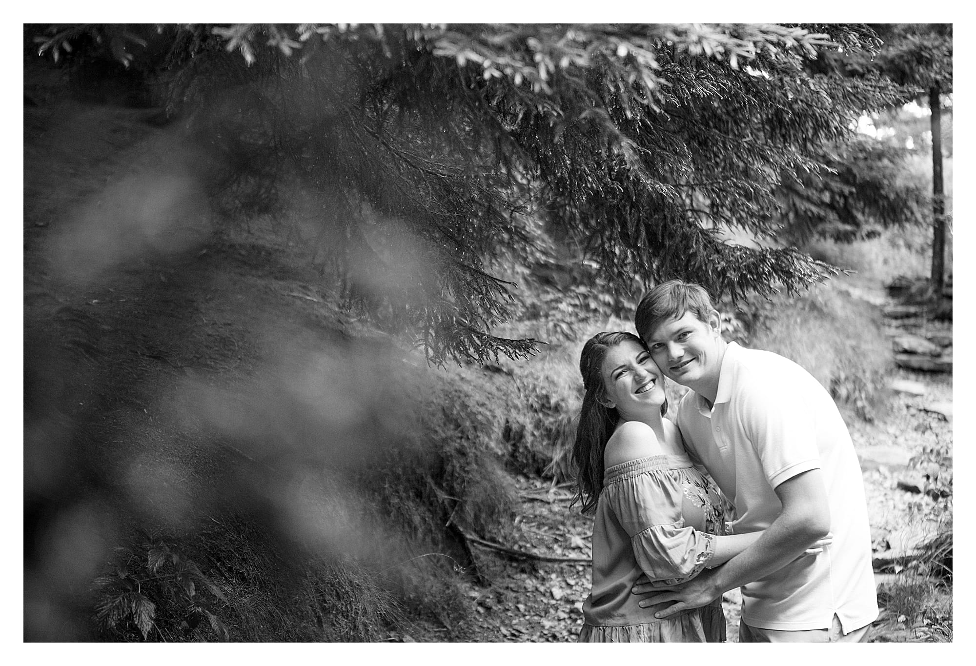 Black and white photo of young engaged couple hugging laughingly while smiling at camera
