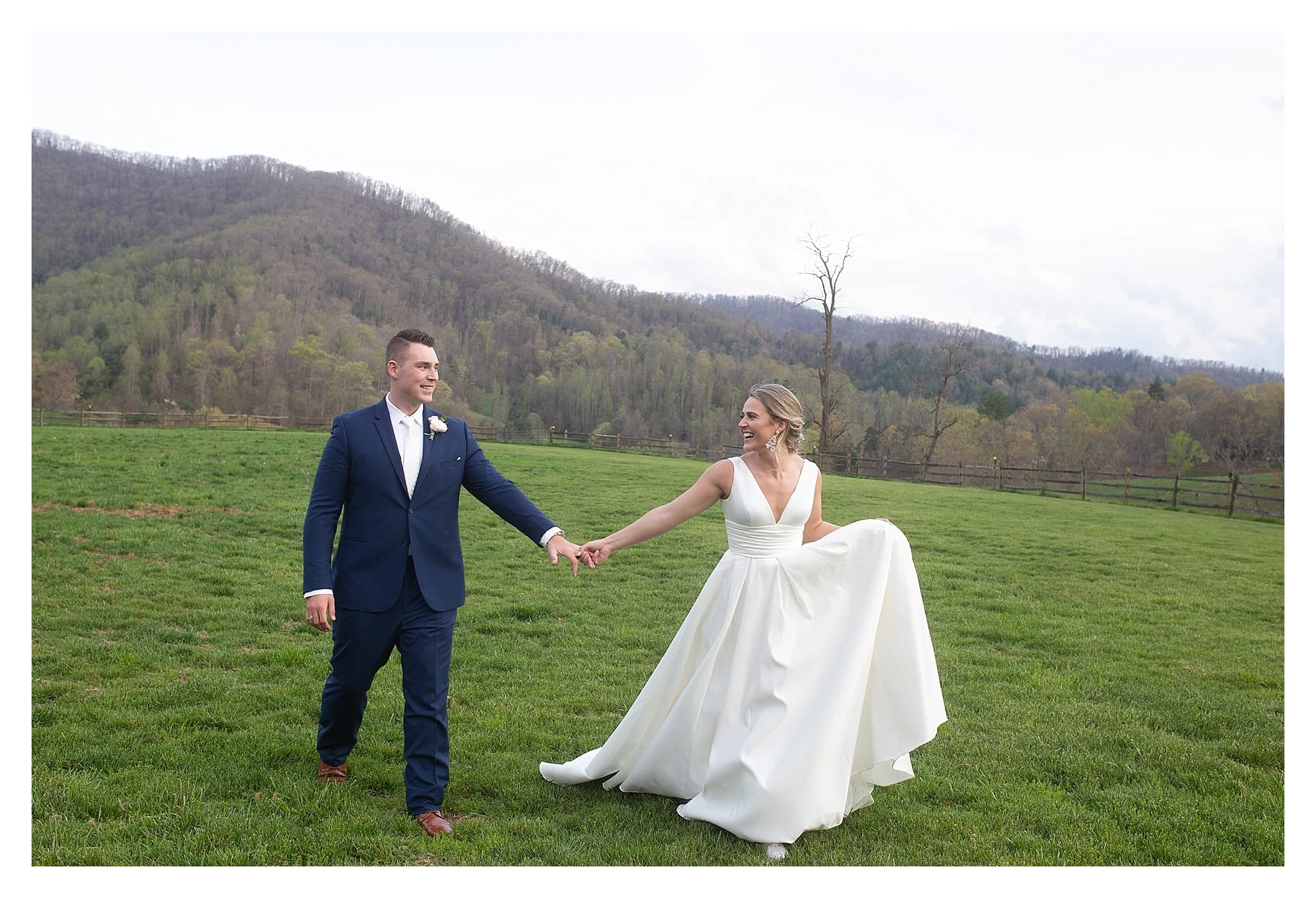 Bride and groom holding hands in grassy field