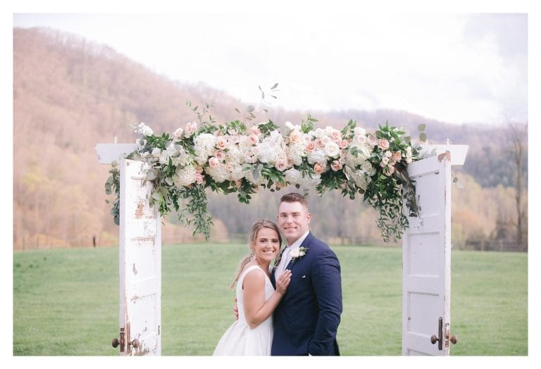 Bride and groom posing under wedding arbour of cream and peach flowers outdoors in grassy field