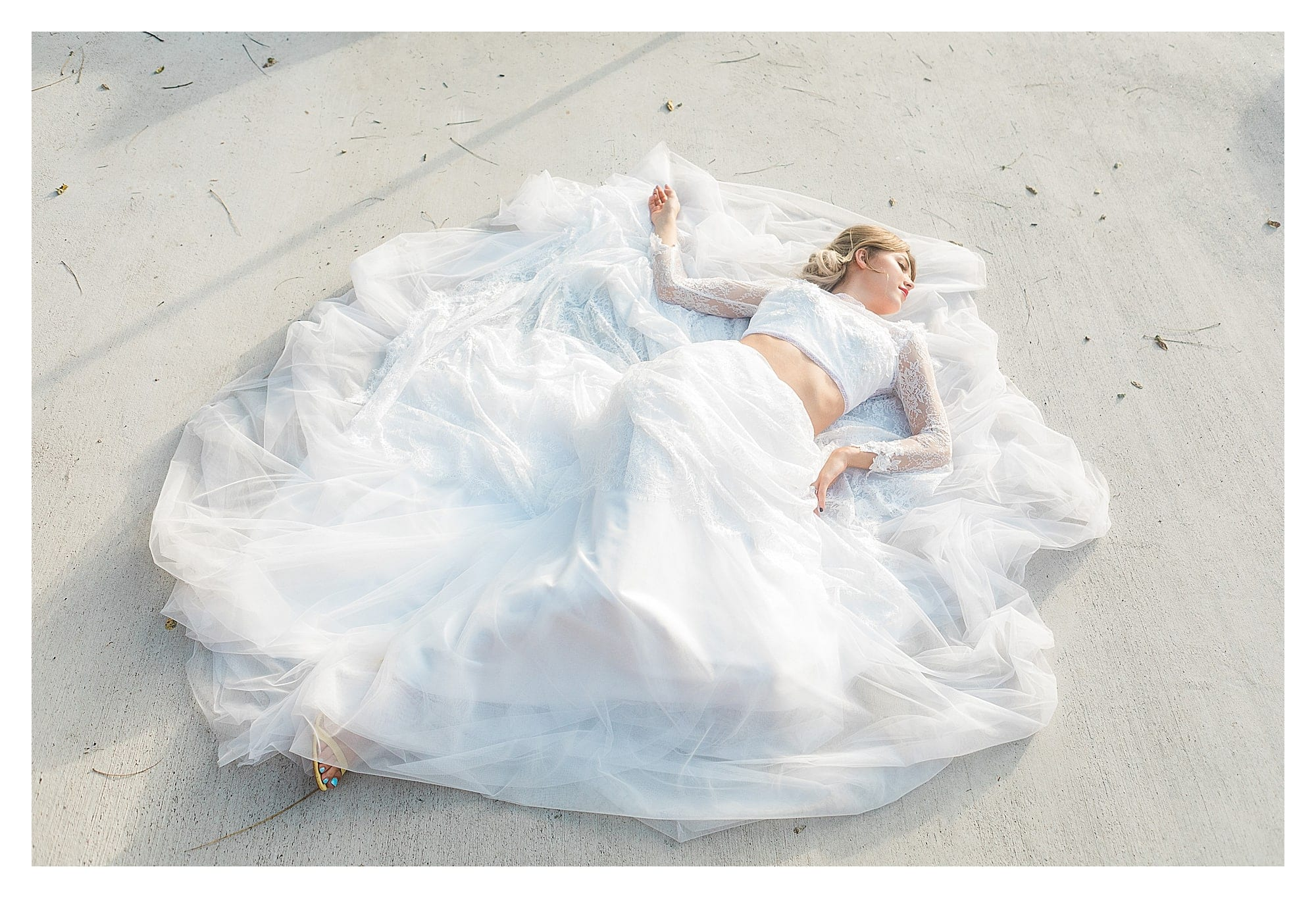 Bride wearing two piece white lace wedding dress laying on concrete posing