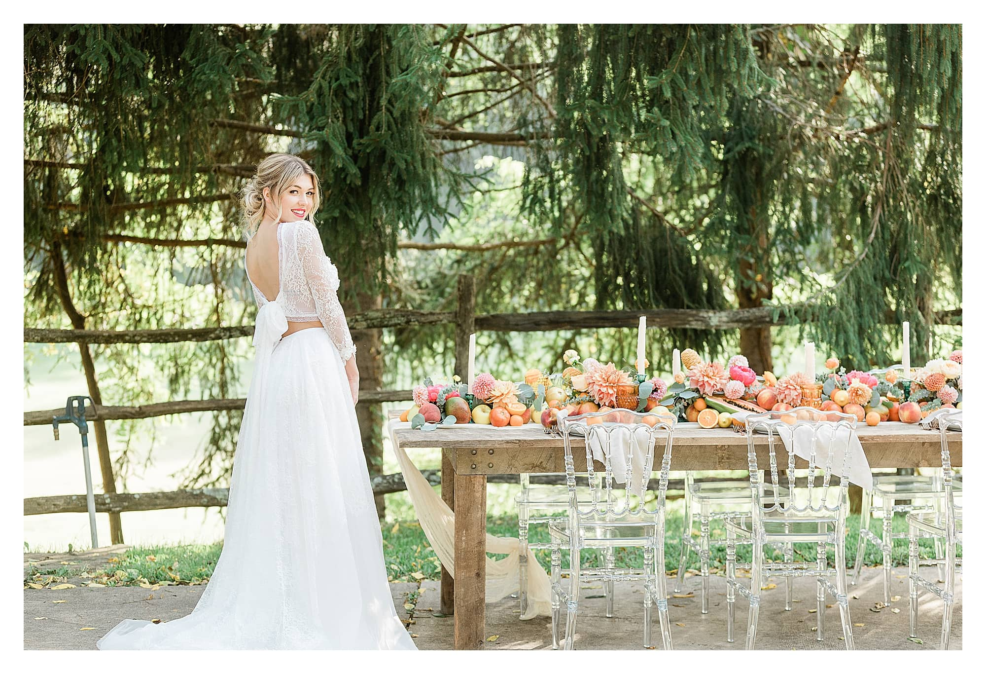 Rustic wooden table and clear plastic chairs with peach, pink and yellow citrus fruits as centrepiece down center of table with white candles with bride in white two piece lace gown standing beside smiling