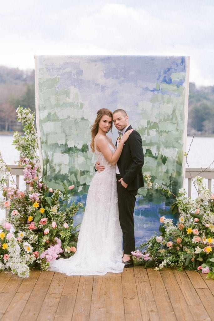 Bride and groom with arms around one another smiling at camera while standing in front of white, green and blue painted canvas backdrop on deck over looking a lake