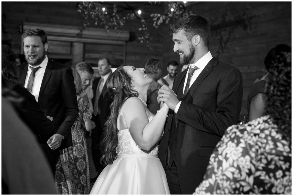 Black and white reception photo of the bride and groom dancing.